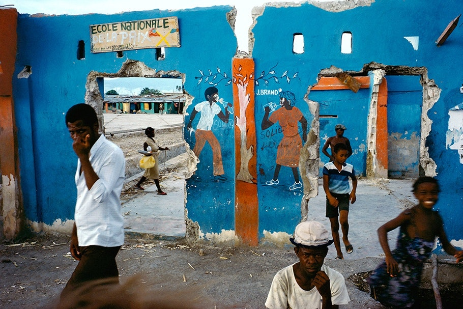 Children in front of a blue run down school wall with murals.
