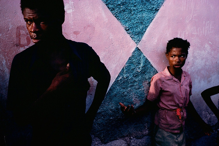 Two people in front of a pink and blue wall.