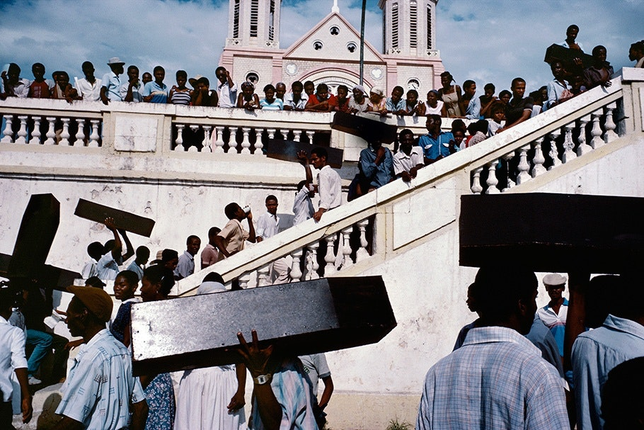 A crowd with coffins in front of a church.