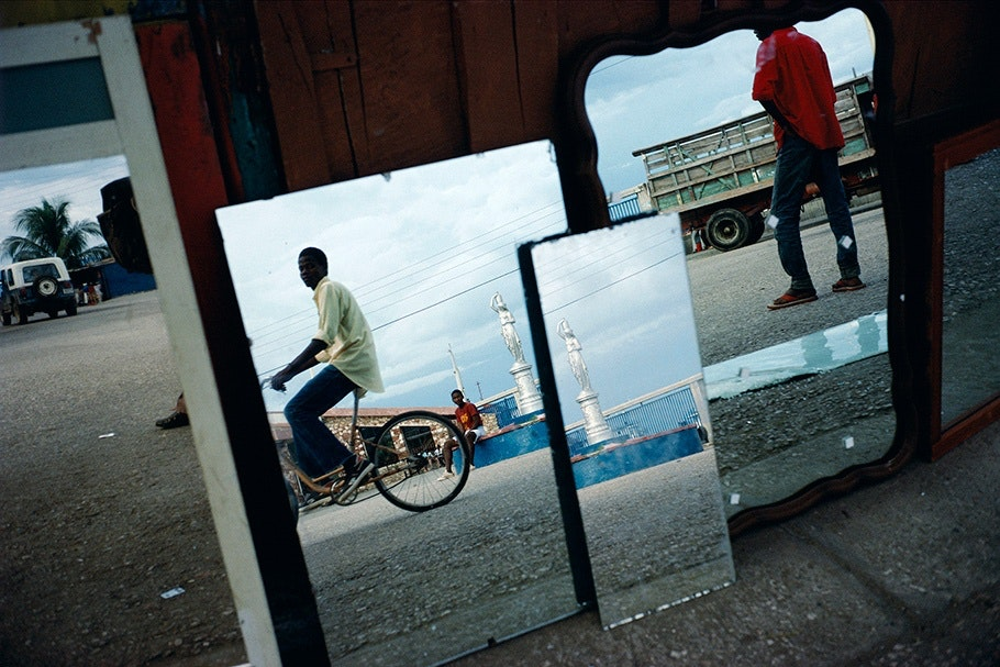 A street scene with a bicyclist reflected in mirrors.
