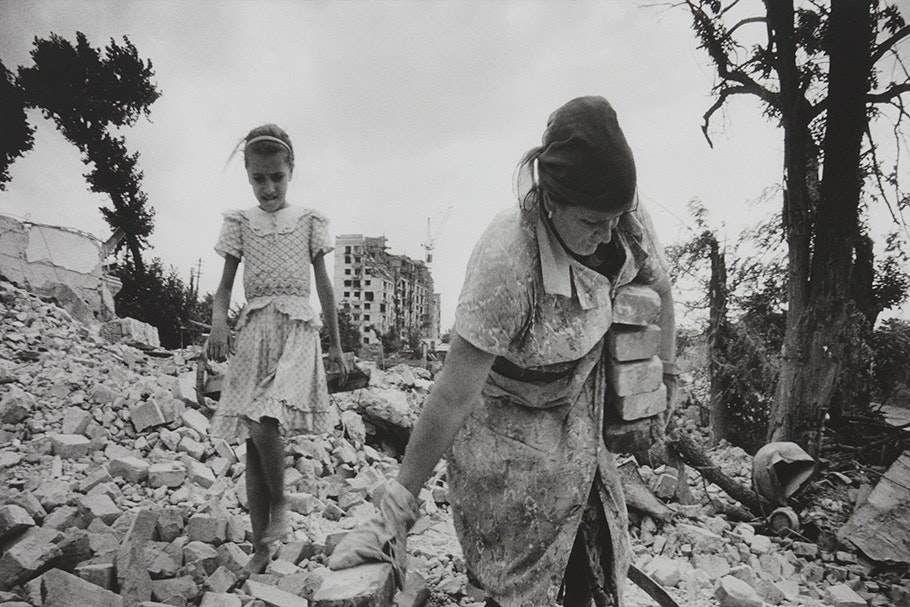 Girl with woman carrying bricks