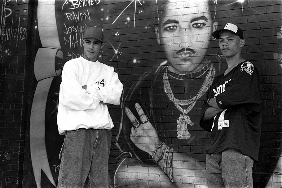 Two teenage boys in front of a mural.