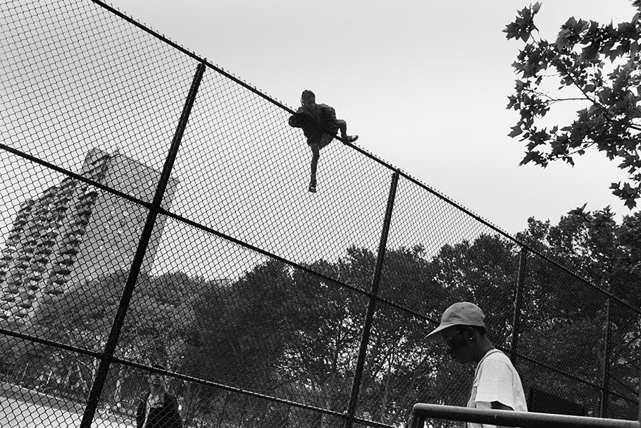 A boy climbing a fence.