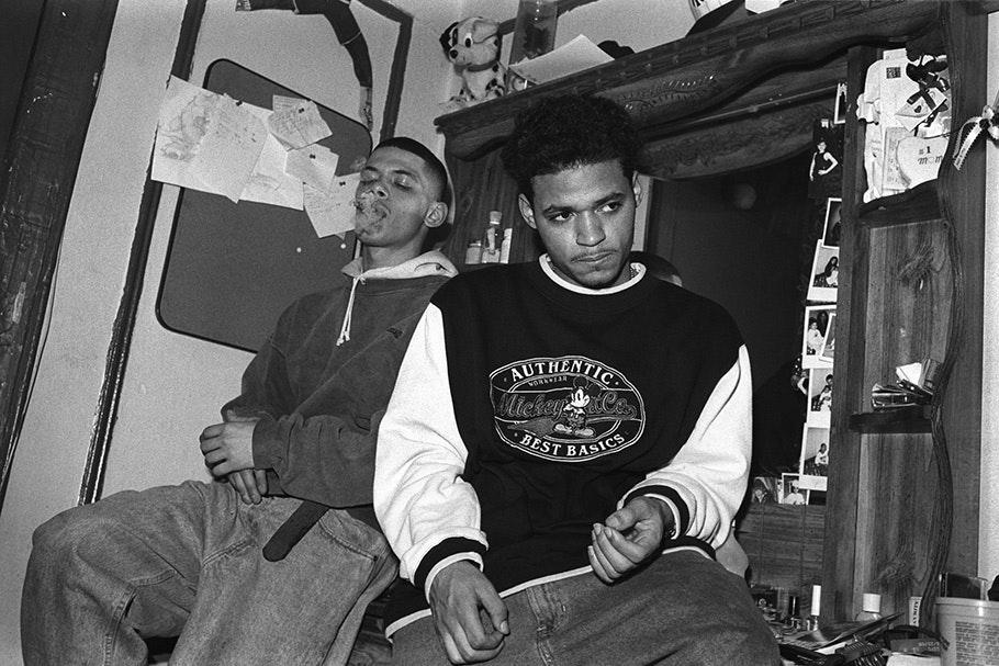 Two teenage boys inside, one smoking.