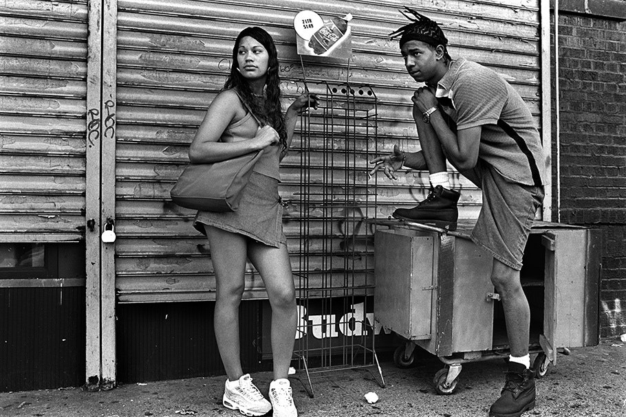 Teenage boy and girl in front of a closed store.