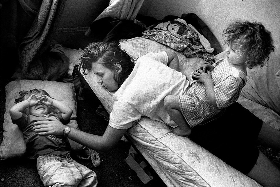 A mother and daughter on a bed comforting a crying boy below.