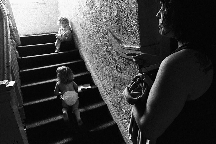 A women watching two children on a staircase.