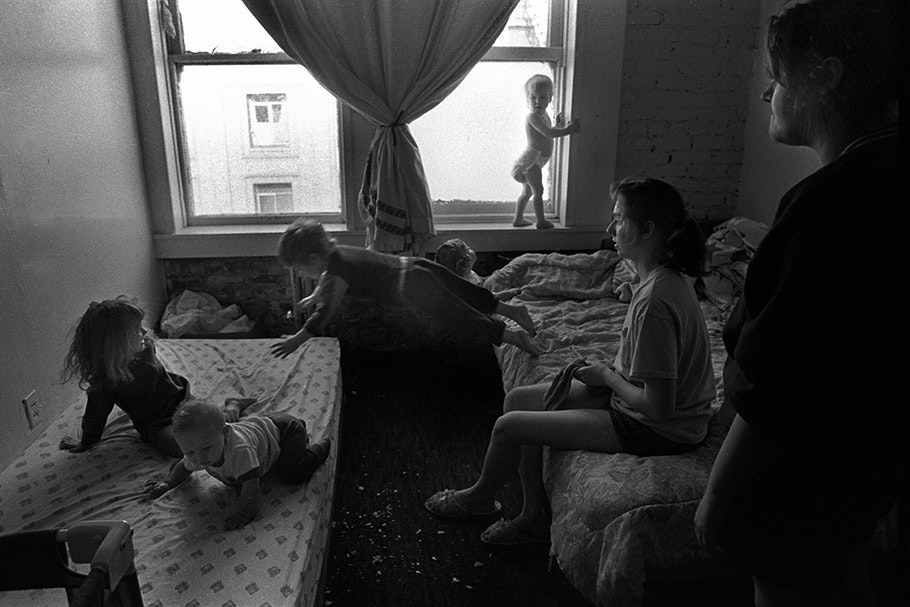 Women and children playing in a bedroom, with a child jumping between beds.