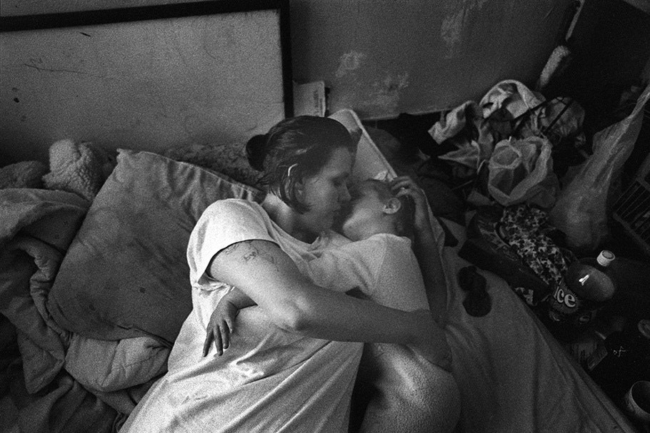A mother and child hug on a bed.