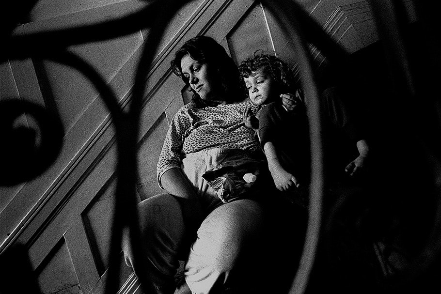 Mother and child viewed through a staircase railing.