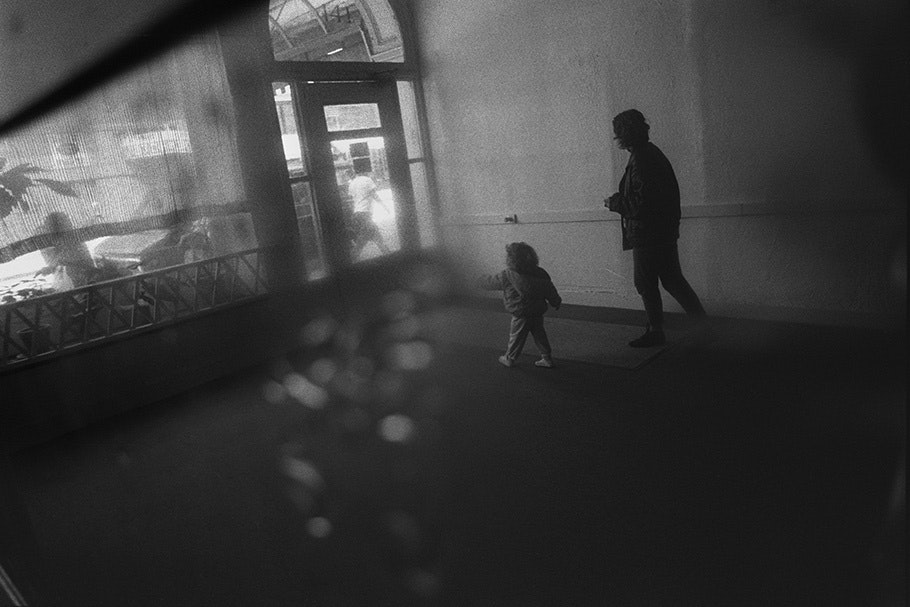 A mother and daughter walk toward a hotel door.