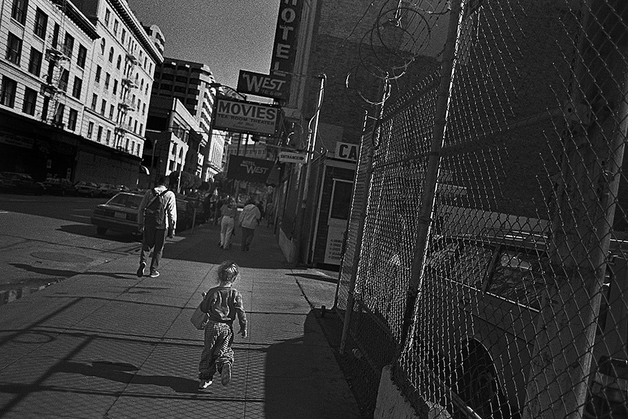 A girl walks down a street next to a chainlink fence.