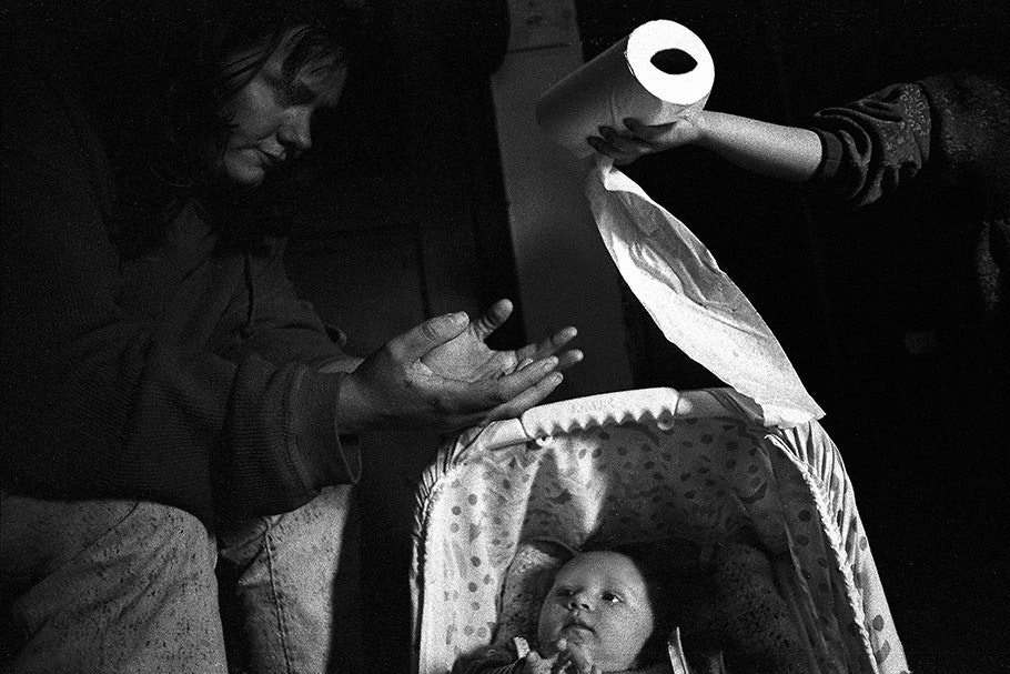 Hands passing a roll of toilet paper over a baby.