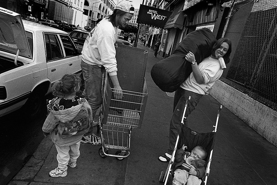 A family moves belongings with a shopping cart.