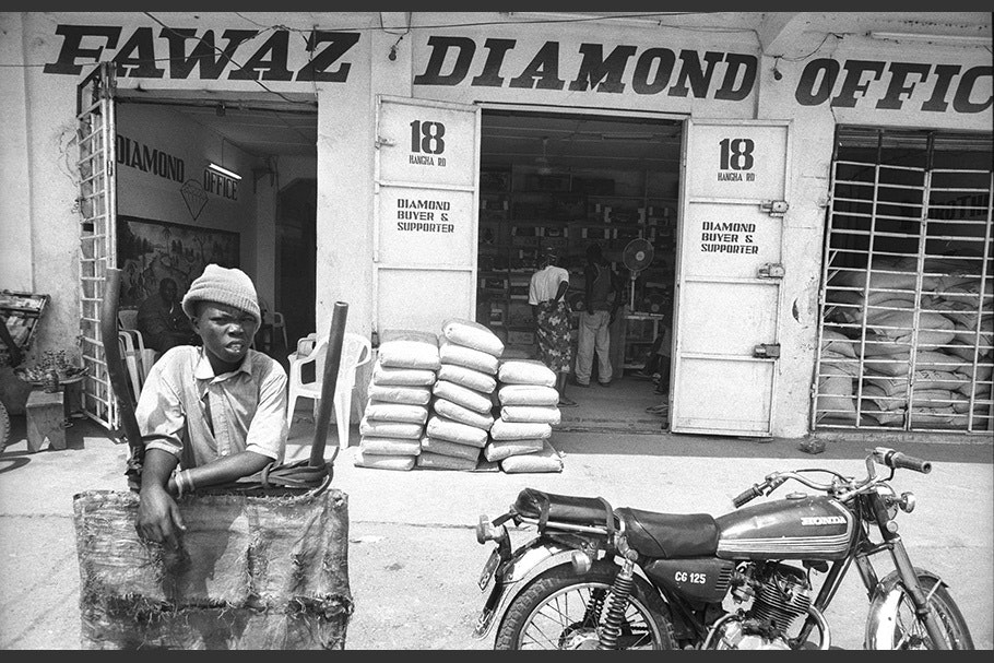 A person and a motorcycle in front of a diamond shop.