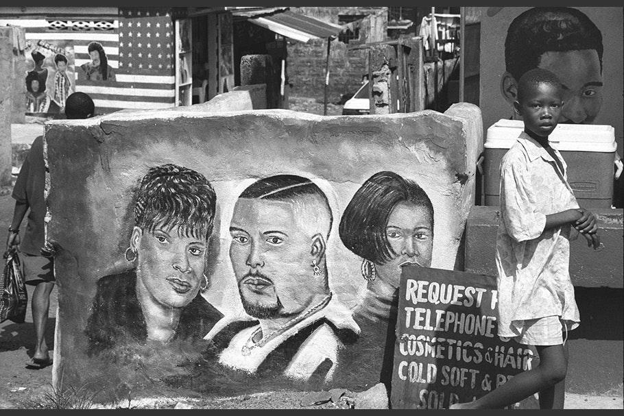 A boy walks by a hairdresser's mural.