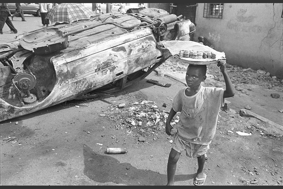 A boy walking by an overturned car carrying a tray on his head.