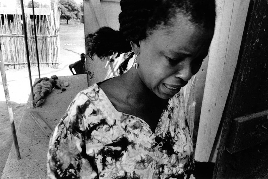 A woman crying with a body in the background.