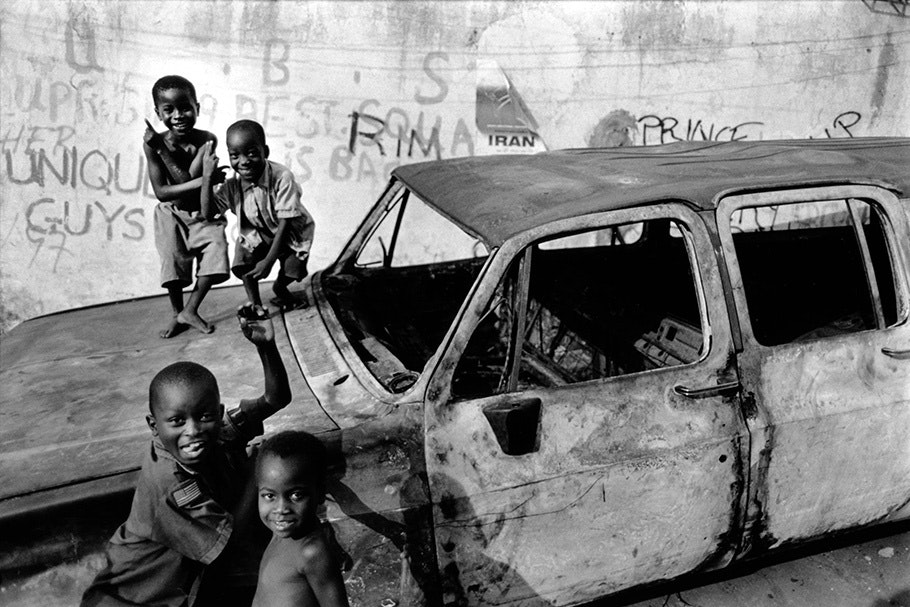 Kids playing on a burnt out car.