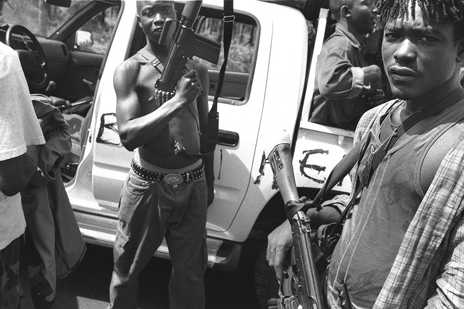 Armed men in front of a pickup truck.