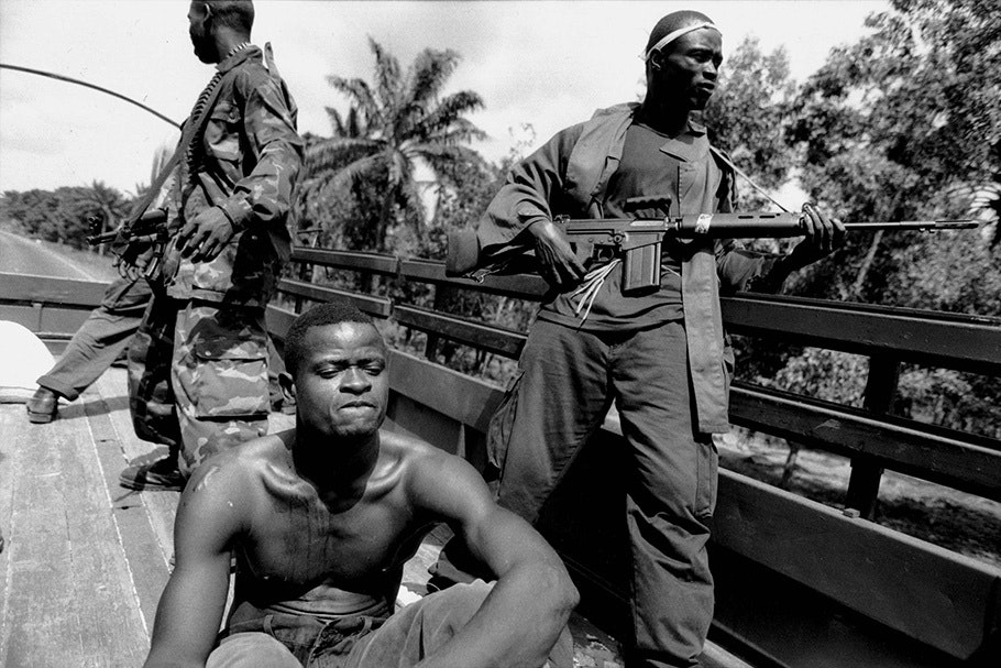 Soldiers transport a prisoner in the back of a truck.