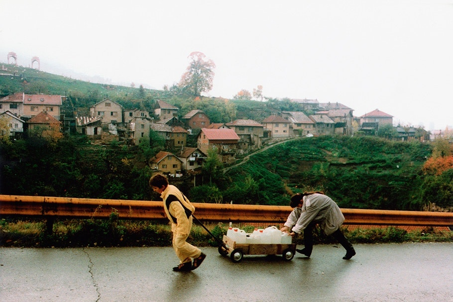 People carrying water jugs in a wagon.