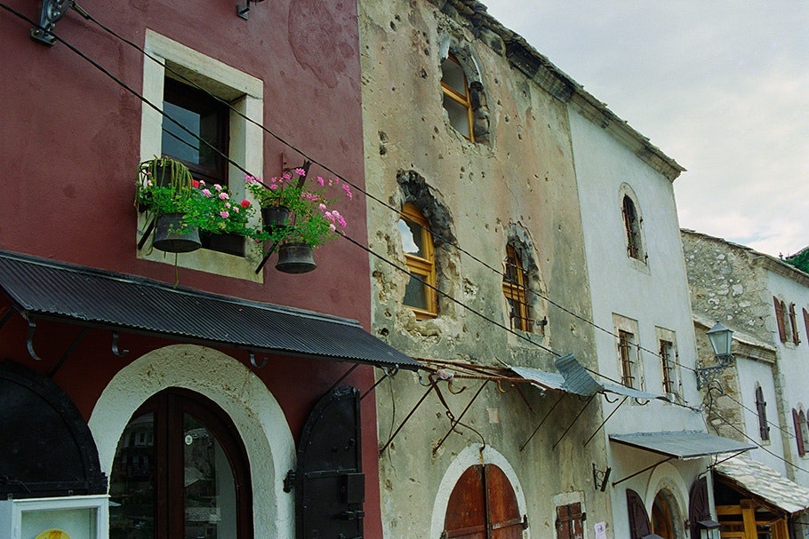 The façades of homes with flowers in the windows.