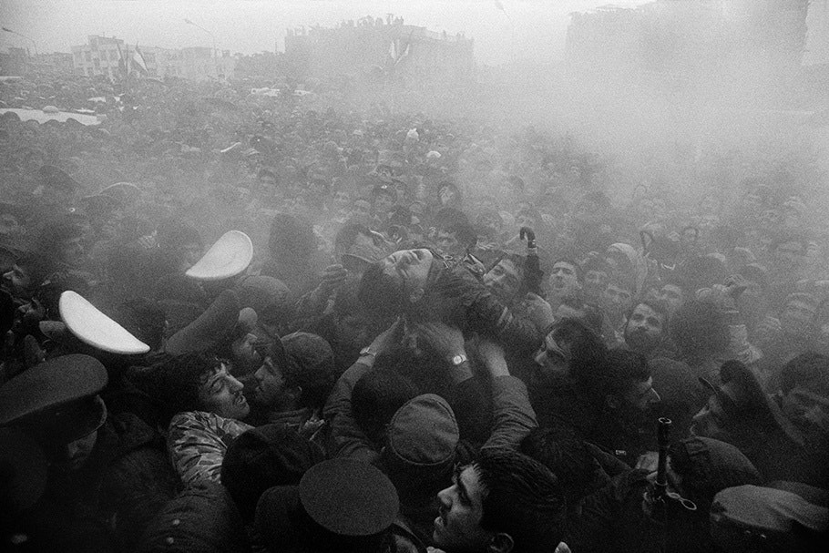 A man is passed over a crowd in a haze.