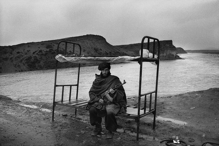 An armed man on a bunk bed in front of a landscape.