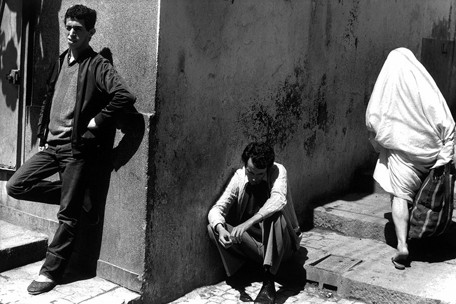 Three men outside the corner of a building.