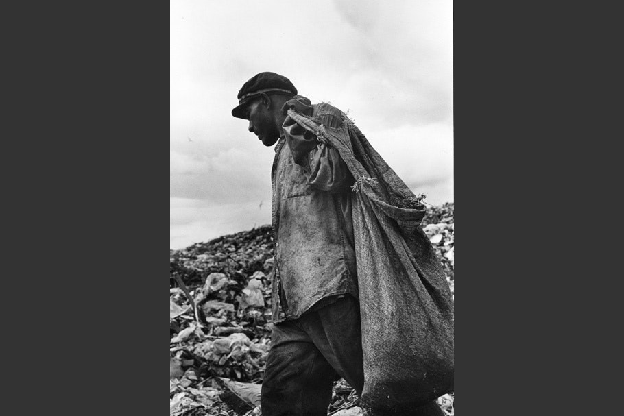 A man carrying a sack in a garbage dump.