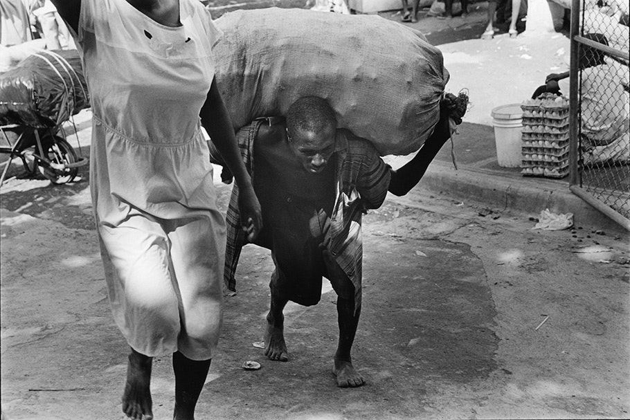 A man carrying a heavy sack on his back.