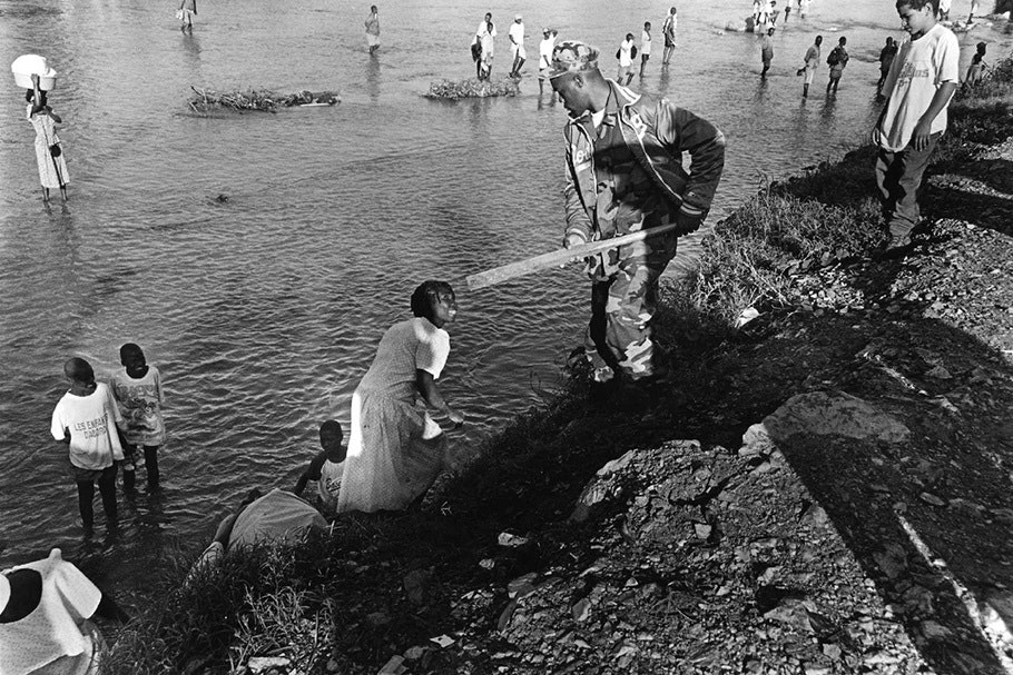 A guard holding a wood plank stands near a woman by the of water.