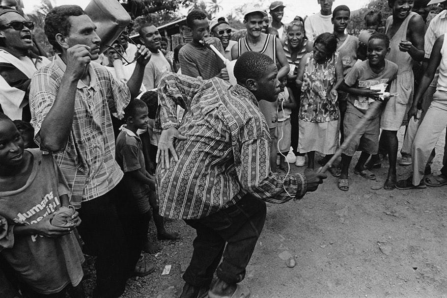 A circle of people surrounding a dancing man.