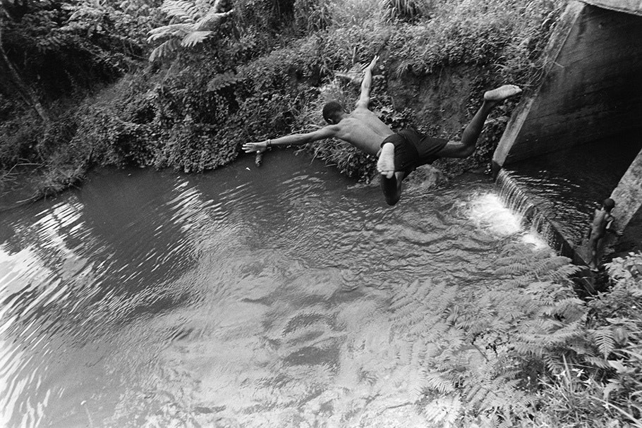 A boy jumping into a swimming hole.