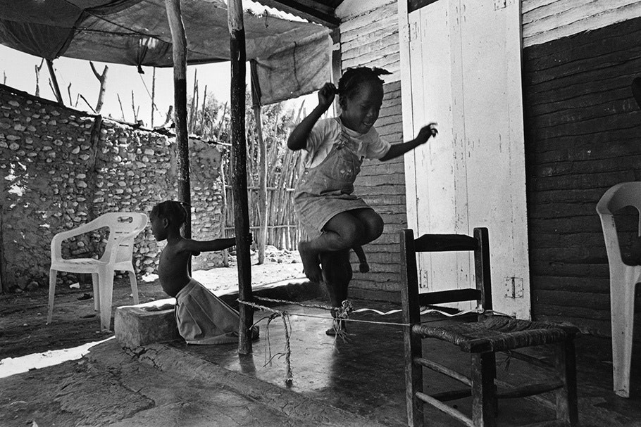 Children jumping rope on a porch.