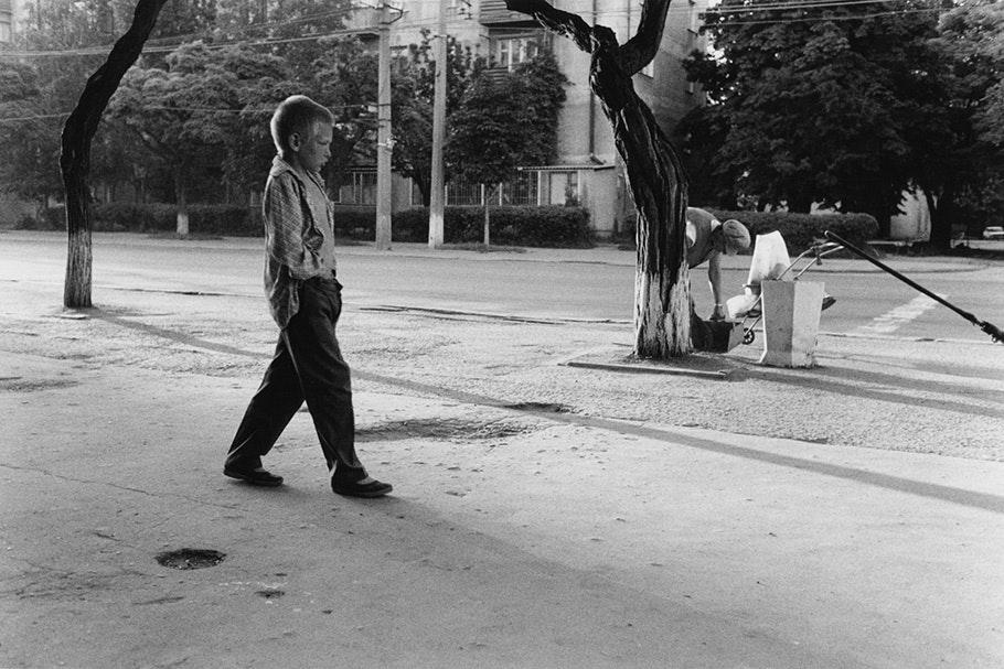 A boy walking down a street.