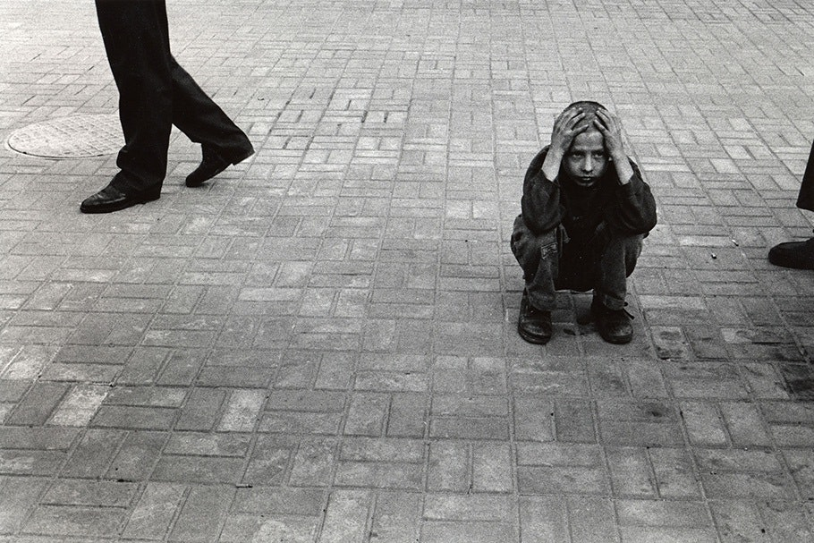 A boy crouching on the ground.