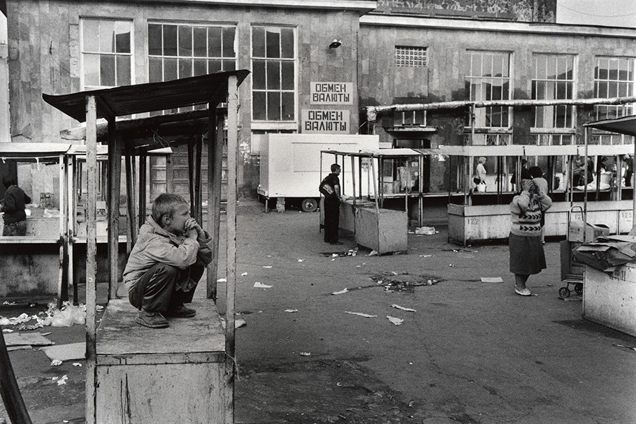 A boy with empty market stalls.