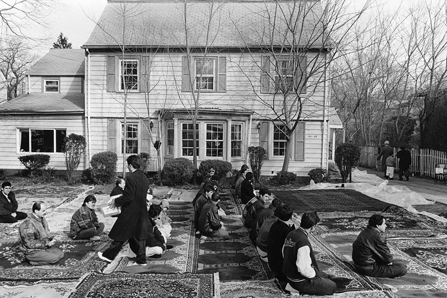 Muslim men praying on the lawn of a house.