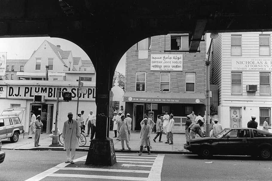 Muslim men under an elevated subway track.