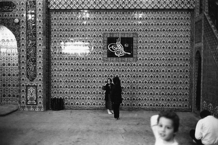 Children in front of a patterned wall.