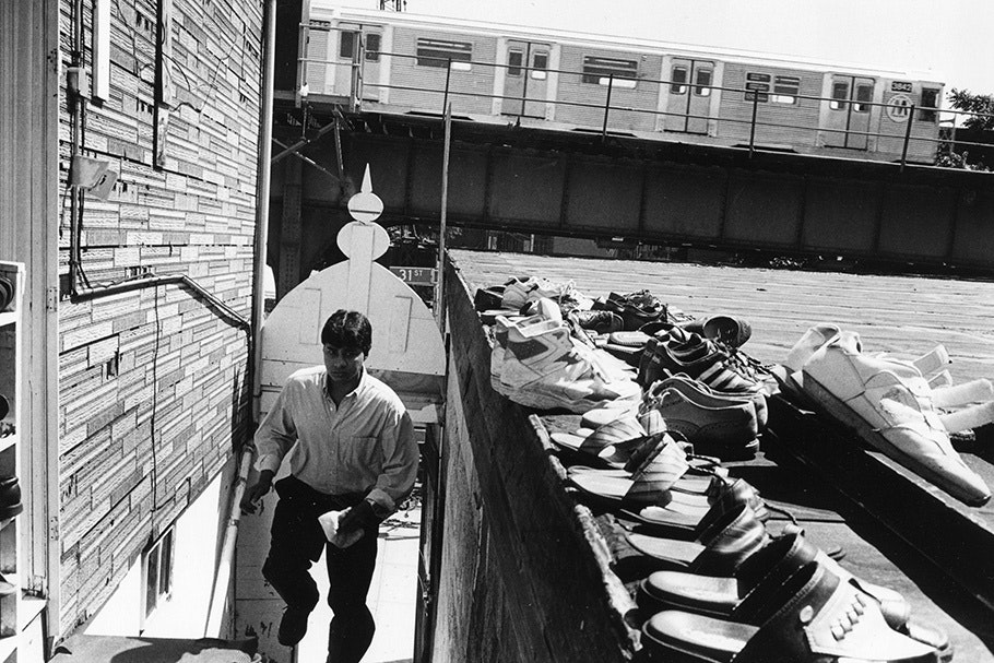 A man with a row of shoes and a subway train.
