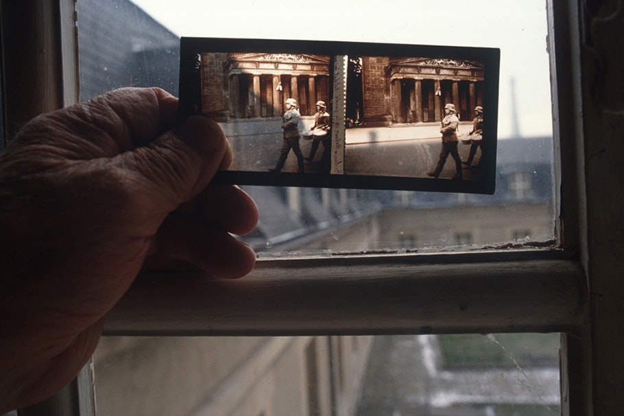 A hand holding color film in front of a window.