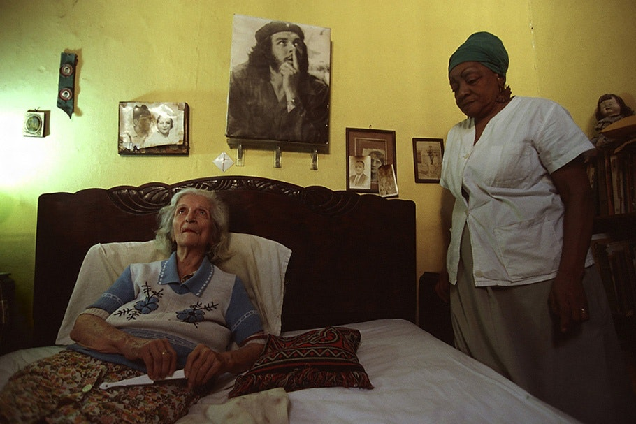 An elderly woman in bed with her caregiver nearby.
