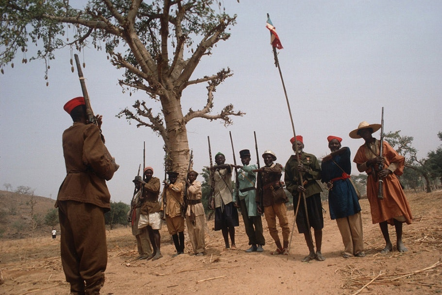 A row of armed men at a funeral ceremony.