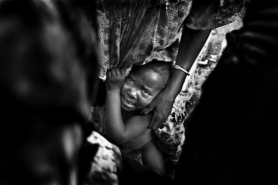 A crying child clings to her mother.