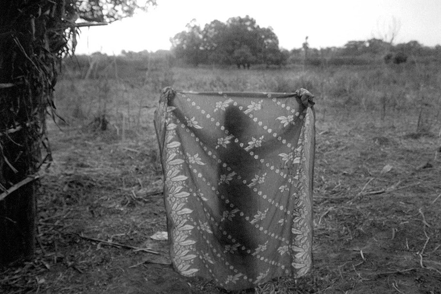 A person silhouetted behind a patterned sheet.