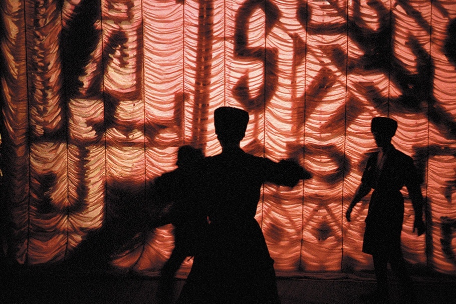 Performers in front of a red illuminated backdrop.