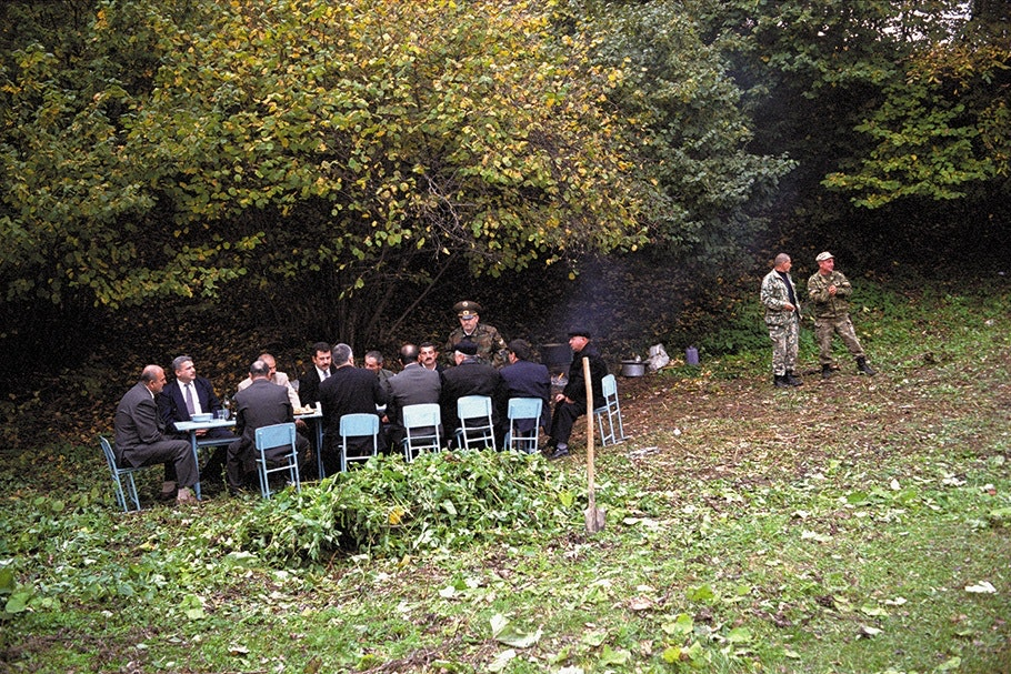 Men in suits seated at an outdoor table.